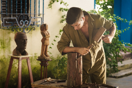 carves: Young man at work learning craftsman profession, working with hammer and chisel. The artist carves a raw block of wood to make a wooden statue