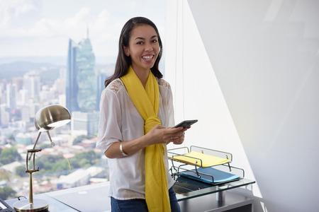 mujer trabajadora: multiétnica mujer hispana china joven que se inclina sobre la mesa en un moderno edificio de oficinas, con una hermosa vista de la ciudad en el fondo. Ella sostiene un teléfono móvil y sonríe a la cámara