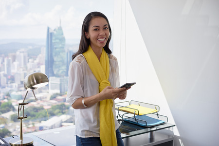 working woman: Young multiethnic Chinese Hispanic woman leaning on table in a modern office building, with a beautiful sight of the city in background. She holds a mobile phone and smiles at camera Stock Photo