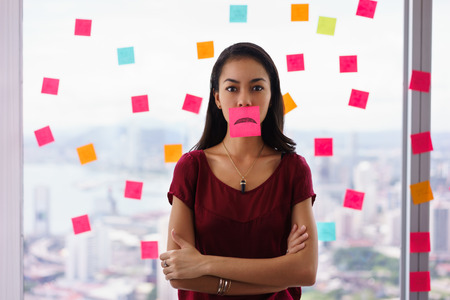 sticky: Mixed race woman working in modern office with reminders on skyscraper window. The girl feels stressed, holds a sticking note with sad emoticon on mouth.