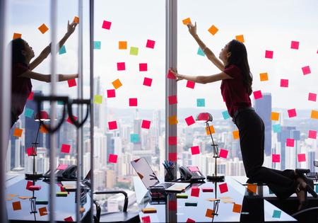 Gemengd ras secretaresse werken in een modern kantoor in wolkenkrabber, plakken zelfklevende notities met taken op het raam. Het meisje voelt zich gestresst en overweldigd