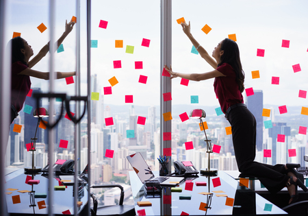 Mixed Rennen Sekretärin im modernen Büro in Wolkenkratzer arbeiten, Haftnotizen mit Aufgaben auf Fenster kleben. Das Mädchen fühlt sich gestresst und überwältigt