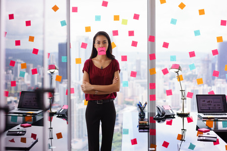 reminder concept: Mixed race woman working in modern office with reminders on skyscraper window. The girl feels stressed, holds a sticking note with sad emoticon on mouth.