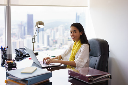 office documents: Portrait of mixed race business woman sitting in modern office in skyscraper. The secretary writes on laptop pc and smiles at camera. Medium shot