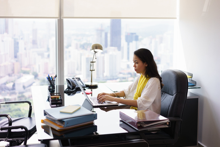 modern businesswoman: Adult businesswoman sitting in modern office in skyscraper. The secretary writes on laptop pc with serious expression. Wide shot Stock Photo