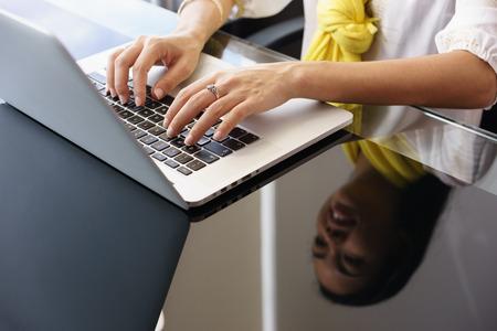 tecnologia: Primo piano di mani di giovane donna adulta di lavoro come assistente in ufficio moderno. La donna di affari scrive sul pc portatile e sorride. Riflessioni sul tavolo