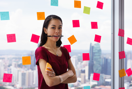 Portrait of proud assistant with pen in mouth. The mixed race woman stands in modern office against a window full of adhesive notes with tasks