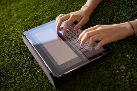 Closeup view of young woman writing on tablet pc on grass, typing an email on digital screen.