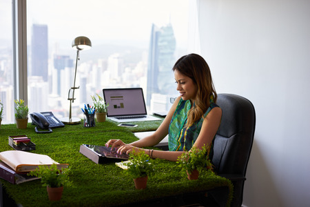 Concept of ecology and environment: Young business woman working in modern office with table covered of grass and plants. She types on tablet pc