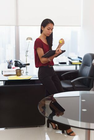 stress ball: Office worker leaning on desk. The woman reads an email on tablet computer and holds an anti-stress yellow ball. She feels stressed and nervous