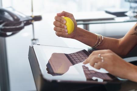 Empleado de oficina escribiendo correo electrónico en la computadora de la tableta. La mujer está estresada y nerviosa, tiene una bola de color amarillo en la mano antiestrés