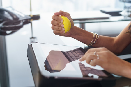 estrés: Empleado de oficina escribiendo correo electrónico en la computadora de la tableta. La mujer está estresada y nerviosa, tiene una bola de color amarillo en la mano antiestrés
