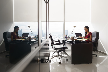 ejecutivo en oficina: Adult businesswoman sitting in modern office in skyscraper. The secretary is concentrated and writes email on tablet computer. Wide shot Foto de archivo