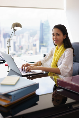 medium shot: Portrait of mixed race business woman in casual clothing, sitting in modern office. The secretary writes on laptop and smiles at camera. Medium shot