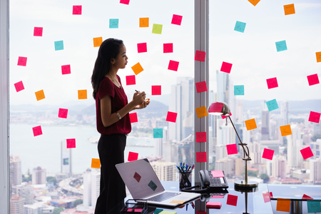 order chaos: Mixed race secretary working in modern office in skyscraper, writing and sticking adhesive notes with tasks on window.