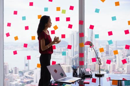 secretaria de la raza mezclada que trabaja en la oficina moderna en rascacielos, la escritura y pegando notas adhesivas con las tareas en la ventana.