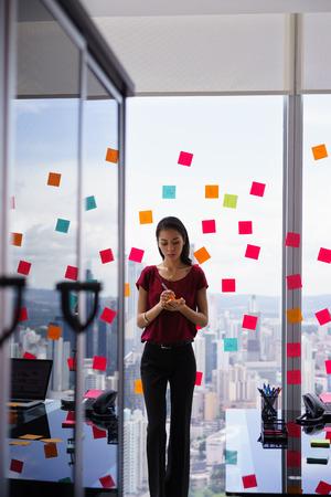 secrétaire des courses mixtes travaillant dans le bureau moderne gratte-ciel, l'écriture et coller des notes adhésives avec des tâches sur la fenêtre.