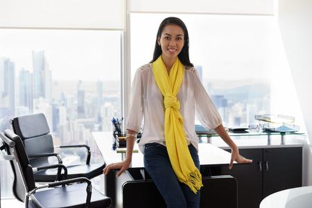 Jonge multi-etnische Chinese Spaanse vrouwelijke ondernemer leunend op tafel in een modern kantoorgebouw, met zicht op de stad. Ze kijkt naar de camera en glimlacht gelukkig