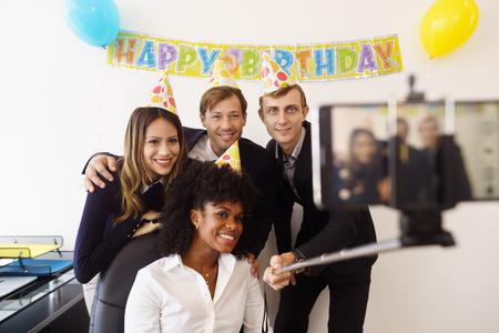 Femme d'affaires célébrer son anniversaire et de faire une fête avec des collègues dans son bureau. Un ami tient son téléphone avec un bâton de selfie et prend des photos de ses collègues de travail en souriant. plan moyen Banque d'images - 51897124