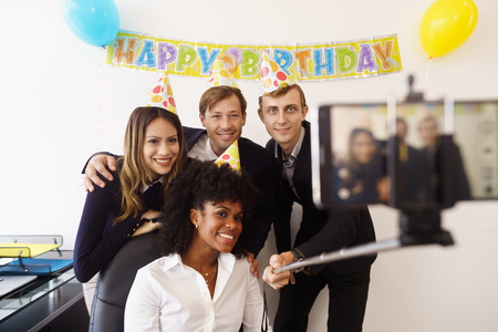 Zakenvrouw viert haar verjaardag en het doen van een feestje met collega's in haar kantoor. Een vriend houdt zijn telefoon met een selfie stok en neemt foto's van zijn collega-collega's lachend. medium Stockfoto