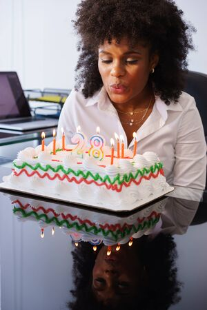 Business person celebrating 28 years and doing a party in office. She blows out the clandles on birthday cake and smiles for joy
