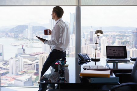 reviewing: Adult businessman sitting on desk in modern office and reading news on tablet pc with a cup of coffee. The man looks out of the window and contemplates the city and skyscrapers.