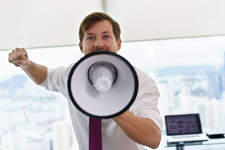 office man: Angry businessman with megaphone in modern office looking at camera. The angry man screams and fights for his labor rights.