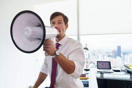 megafono: Joven trabajador de oficina ejecutiva que sostiene el megáfono y hablar a la cámara con confianza. espacio de la copia