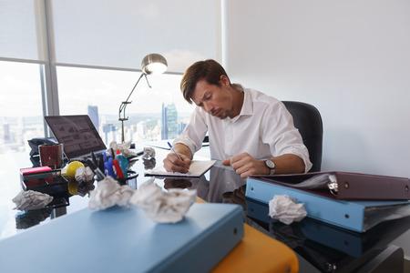 gerente corporativo en la oficina moderna intenta escribir una carta de trabajo. El hombre se siente frustrado y sigue atornillado de papel en el escritorio