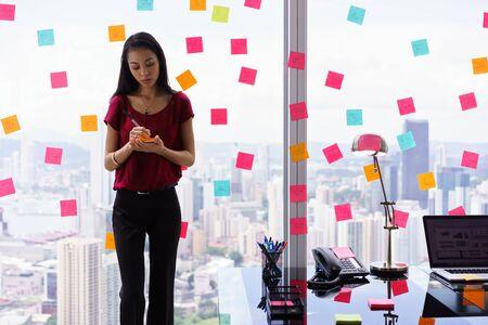 mucha gente: mujer joven que trabaja como secretaria en la oficina, apoyándose en gran ventana de rascacielos. Ella escribe notas adhesivas con las tareas en la ventana.