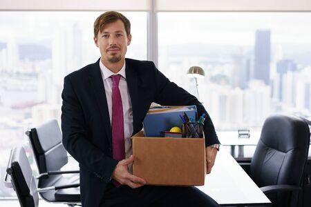 relocating: Businessman recently hired for corporate job moves into his new executive office with a view of the city. He leans on desk and smiles at camera happy.