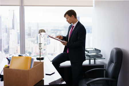 folder with documents: Businessman recently hired for corporate job moves into his new office. He takes out a folder from a box and reads documents near a big window, with a view of the city. Stock Photo