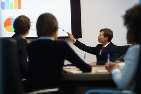 Grupo de hombres de negocios reunidos en la sala de conferencias corporativa, sonríe durante una presentación. Los compañeros de trabajo están examinando los gráficos y diapositivas en un monitor de TV grande Foto de archivo
