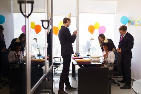 Mujer de negocios la celebración de cumpleaños y hacer una fiesta con los colegas en su oficina. Un amigo con el teléfono móvil toma fotos de ella que soplan hacia fuera clandles en la torta de cumpleaños. plano general