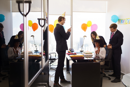 felicitaciones cumpleaÑos: Mujer de negocios la celebración de cumpleaños y hacer una fiesta con los colegas en su oficina. Un amigo con el teléfono móvil toma fotos de ella que soplan hacia fuera clandles en la torta de cumpleaños. plano general Foto de archivo