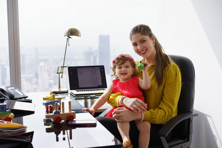 Busy businesswoman with little daughter in office. The executive mom spends time with her child and takes her at work Foto de archivo