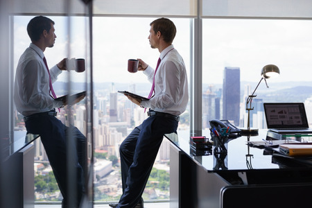 contemplates: Adult businessman sitting on desk in modern office and reading news on tablet pc with a cup of coffee. The man looks out of the window and contemplates the city and skyscrapers.
