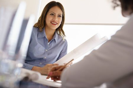 medium shot: Team of two female architects, sitting at desk in office. The women talk and smile reviewing a building plan. Medium shot Stock Photo