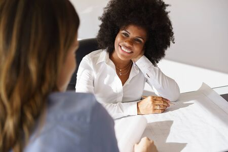 corporate women: Team of two female architects, sitting at desk in office. The women talk and smile reviewing a building plan. Medium shot Stock Photo