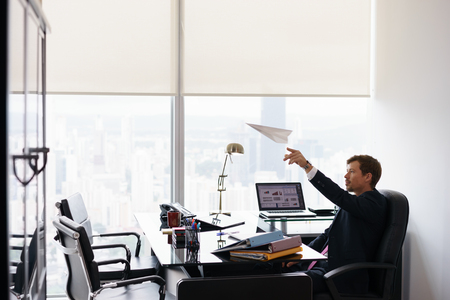 office time: Corporate manager in modern office takes a break and prepares a paper airplane. The bored man dreams of his next vacations and leans back on his chair. Copy space