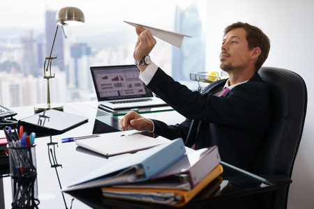 Corporate manager in de moderne kantooromgeving neemt een pauze en bereidt een papieren vliegtuigje. De verveelde man droomt van zijn volgende vakantie en leunt achterover in zijn stoel