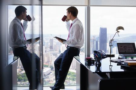 Erwachsener Geschäftsmann auf Schreibtisch im modernen Büro sitzen und Nachrichten mit einer Tasse Kaffee auf Tablet PC zu lesen. Der Mann schaut aus dem Fenster und betrachtet die Stadt und Wolkenkratzern.