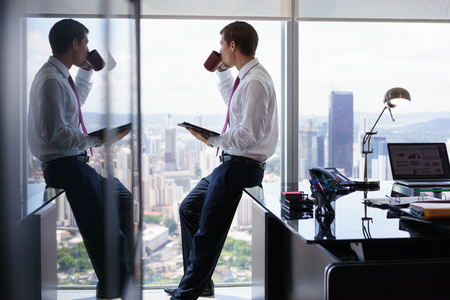hombre de negocios adulto que se sienta en el escritorio en la oficina moderna y la lectura de noticias en el PC tableta con una taza de café. El hombre mira por la ventana y contempla la ciudad y los rascacielos.
