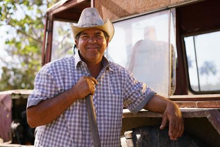 La agricultura y cultivos en América Latina. Retrato de los agricultores hispánico de mediana edad que se sienta orgullosa de su tractor al atardecer, sosteniendo el volante. Él mira a la cámara y sonríe feliz. Foto de archivo