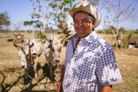 Landwirtschaft und Anpflanzungen in Lateinamerika. Portrait des mittleren Alters hispanische Bauer sitzt stolz in seinem Traktor bei Sonnenuntergang, die Volante halten. Er schaut in die Kamera und lächelt zufrieden.