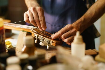 maker: Lute maker shop and classic music instruments: young adult artisan fixing old classic guitar adding a cord and tuning the instrument. Close up of hands and palette