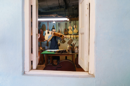 curvature: Lute maker shop and classic music instruments: young adult artisan fixing old classic guitar. The man looks carefully at bridge and arm to check the wood curvature. Full length