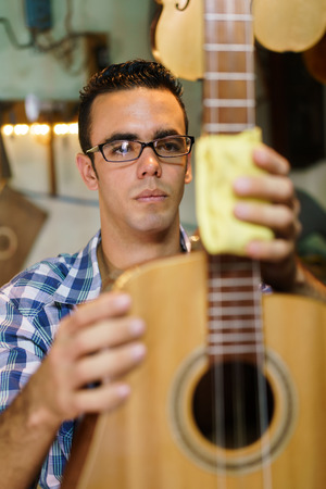 medium shot: Lute maker shop and acoustic music instruments: young adult artisan focused on cleaning and wiping an old classic guitar. Medium Shot Stock Photo