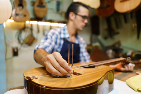 diapason: Lute maker shop and classic music instruments: young adult artisan fixing old classic guitar, tuning the instrument with a metallic diapason. Closeup of hand on guitar body Stock Photo