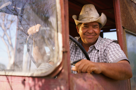 Farming and cultivations in Latin America. Portrait of middle aged hispanic farmer sitting proud in his tractor at sunset, holding the steering wheel. He looks at the camera and smiles happy. Standard-Bild